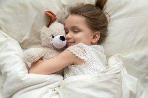 Cute little kid girl hugging teddy bear sleeping lay in cozy bed, happy small child embracing toy fall asleep on soft pillow white sheets covered with blanket having healthy night sleep, top view